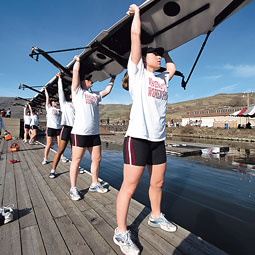 Members of the rowing team prepare to lower a shell into the water. Robert Hubner