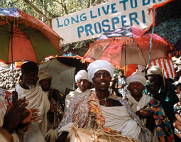 Against the backdrop of a banner made by local villagers, reading 'Long Live to [sic] Bridges to Prosperity,' Ethiopian Orthodox priests celebrate during the bridge inauguration with drums and centuries-old biblical songs of joy. Zoe Keone