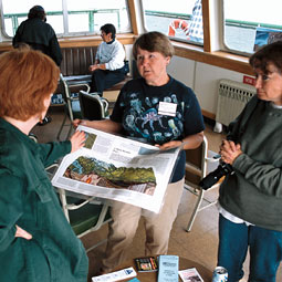 Lyla Snover (white sweatshirt) and Rowena Williamson (with poster) serve as 'ship's naturalists' on the Whidbey Island ferries, talking with visitors about non-point-source pollution and other topics. (c) Laurence Chen