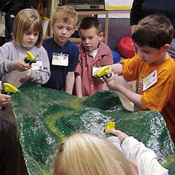 Curlew kindergartners spray spring rain on a model of their watershed.