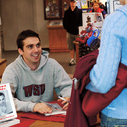 Recent grad Clint Borgen autographs copies of Geneva Nights in the Bookie. Shelly Hanks.