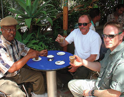 Craig Meredith '87 (right), director of technology for Dominion Trading, sips coffee macchiatos in Awassa, Ethiopia, with Kebede Koomsa (left) and John Slattum, manager of overseas operations.