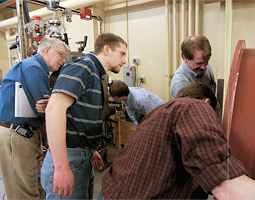 James Asay (left) looks on while the project engineer Kent Perkins ('03 Mech. Engr.), project engineer Kurt Zimmerman ('90 Sci., '92 M.S. Phys.), and guest Dave Strange put the finishing touches on the new two-phase gun in the basement of the Institute for Shock Physics.
