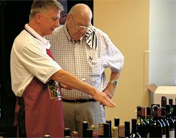 Paul Hooper '53 (right) and another volunteer at the Northwest Enological Society's 2005 judging in Seattle discuss a round of wines being sampled by five expert judges.