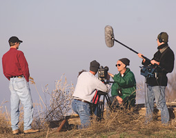 As Paul Johnsgard describes how sandhill cranes return to their roost each night, a crew from Nebraska public television films him for a documentary
