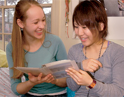 Student Crista Ames and her roommate, Junko Matsumura, look at photographs from Japan.