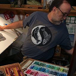 At work in his studio, Troll takes a break from hand coloring to change a CD.