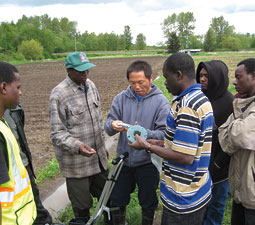 WSU's Bee Cha helps East African refugees assemble a seeder. Photo by Hannelore Sudermann