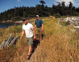Todd Mitchell, '97 MS, and WSU graduate student Steve Hinton walk across Kiket Island. By Ingrid Barrentine