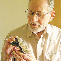 Carl Gustafson holds a mastodon tooth that was part of the 1977 discovery. <em>Courtesy Eric Sorensen</em>