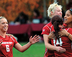 Then-senior Micaela Castain (above, far right) is being hugged by team members after scoring the decisive goal in the 1–0 win over Washington last November. Photo WSU Athletics