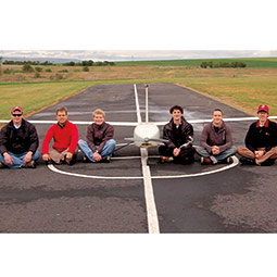 Jacob Leachman, left, and the student group that designed and built the pilotless aircraft Genii, which they flank. <em>Courtesy WSU HYPER Lab</em>