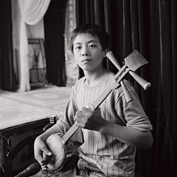 The performers are usually accompanied by a small group of musicians. Here a boy plays a sanxian, a traditional three-stringed instrument.